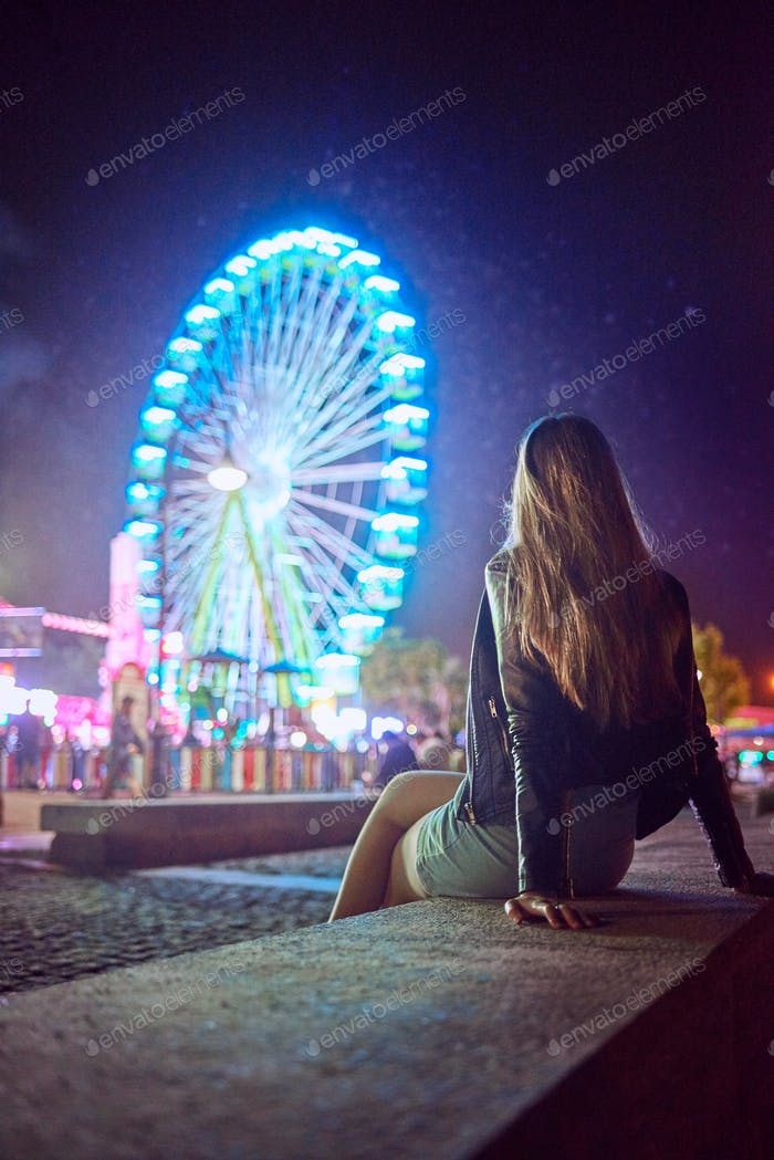 Young woman contemplating a Ferris wheel at night