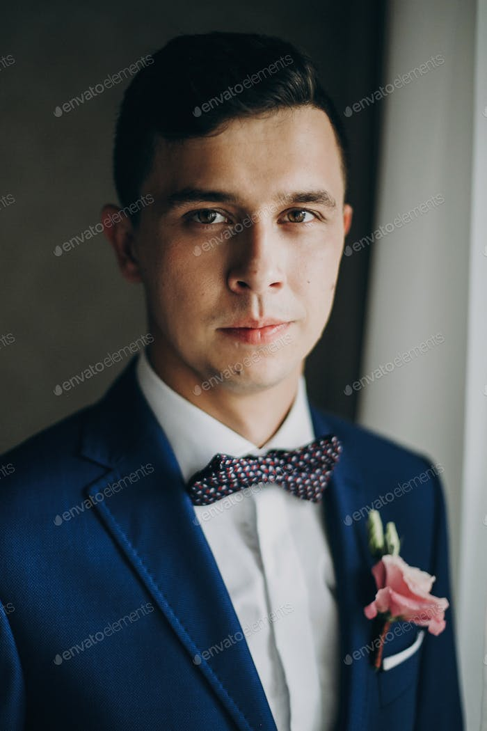 Groom in blue suit, with bow tie and boutonniere with pink rose posing near window