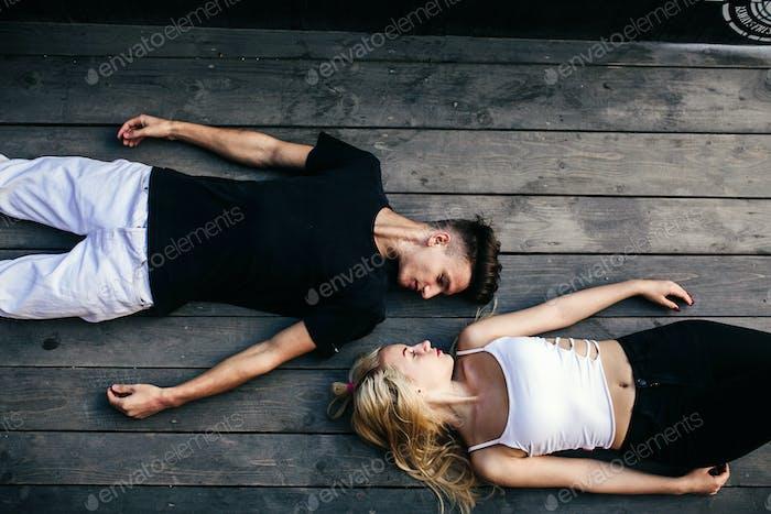 Couple lying together on the hardwood floor