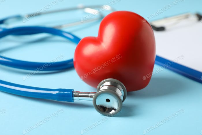 Stethoscope and heart on blue background, close up