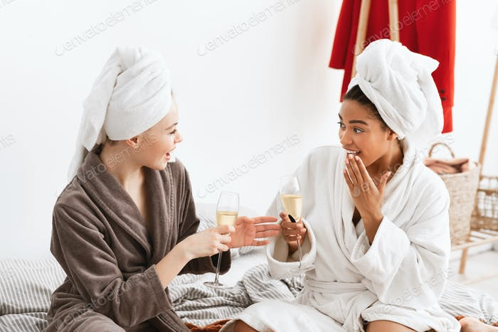 Two young ladies in bathrobes sitting on bed, drinking champagne