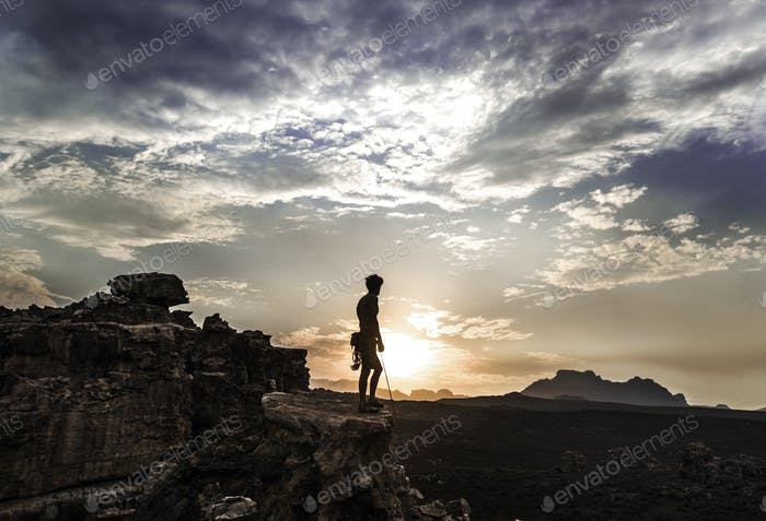 Mountaineer standing on top of a rock formation in a mountainous landscape.