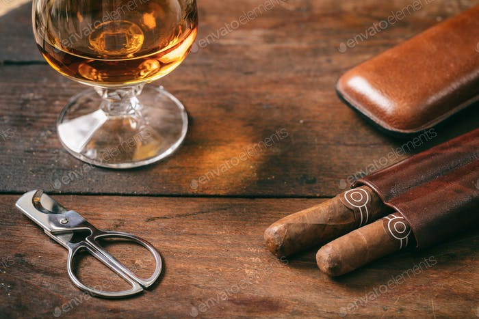 Cuban cigars closeup on wooden desk, blur glass of brandy