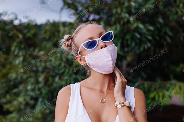 fashion blogger in white crop top, sunglasses and white medical face mask on background of trees
