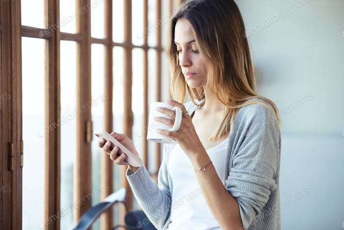 Young woman using her mobile phone while drinking coffee at home