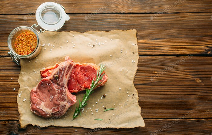 Uncooked meat in seasoning on wooden table