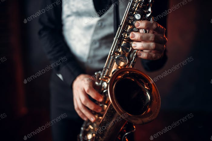 Jazz man hands holding saxophone closeup