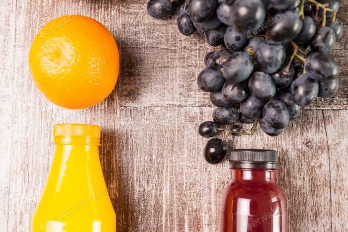 Orange and grape juice in bottles next to two oranges and a grap