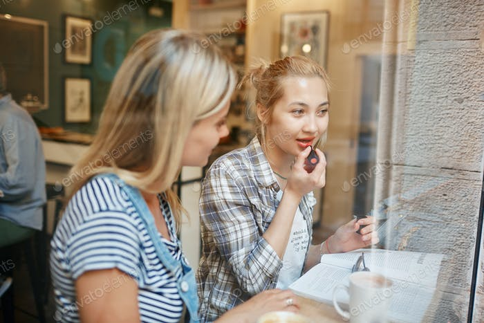 Two female friends sitting inside cafe talking and having coffee