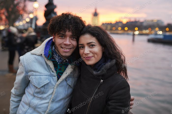 Portrait Of Couple Walking Along South Bank On Visit To London