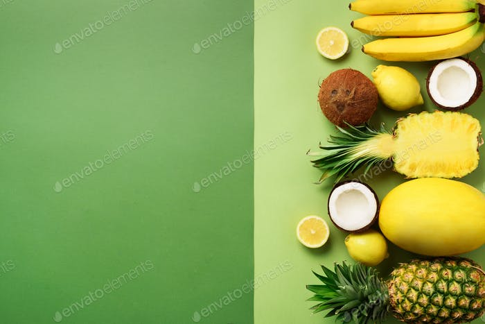 Fresh organic yellow fruits over green background. Monochrome concept with banana, coconut