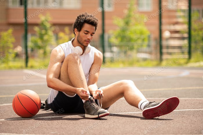 Young athlete sitting on basketball court and tying shoelace of sneaker