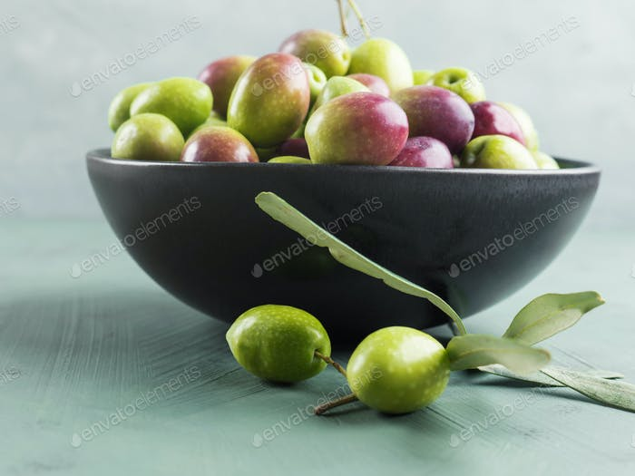Freshly picked raw green olives in black bowl