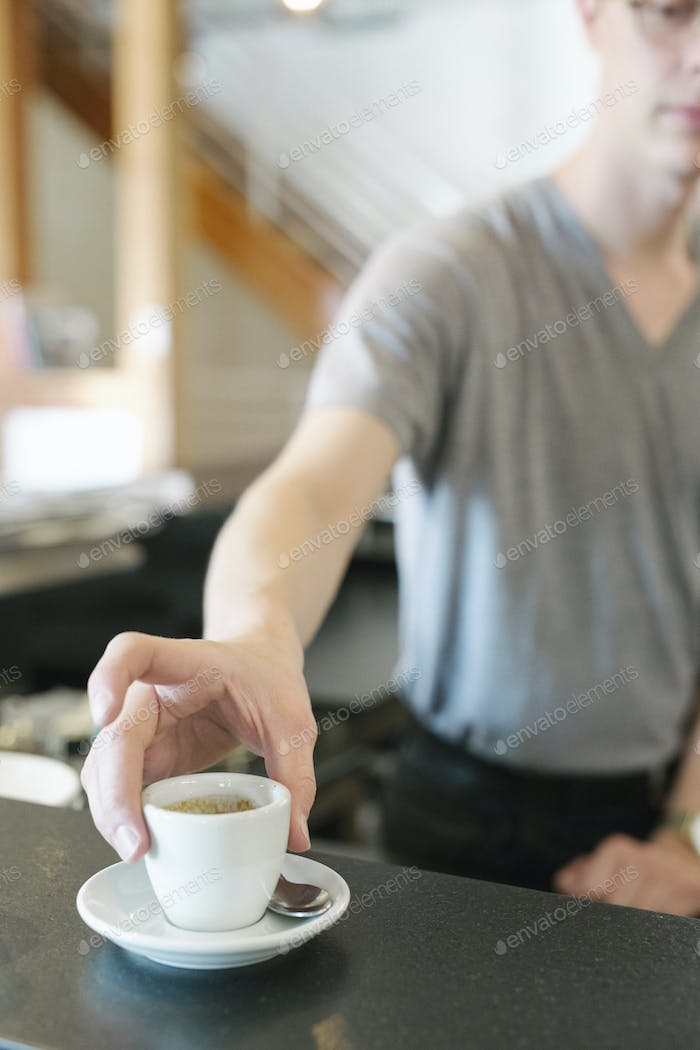 Man standing at a counter in a coffee shop, reaching for a cup of espresso coffee.