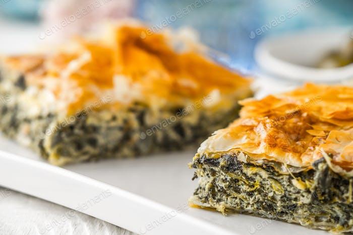 Griechische Kuchen spanakopita auf der weißen Platte mit verschwommenen Zubehör horizontal
