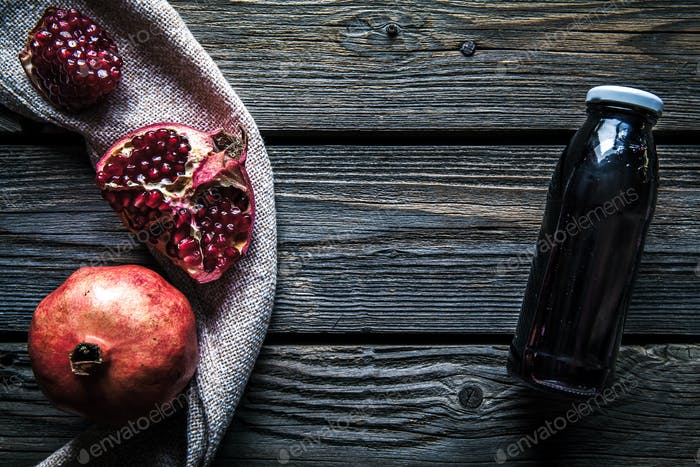 Pomegranate and bottles of essence or tincture on wooden rustic table