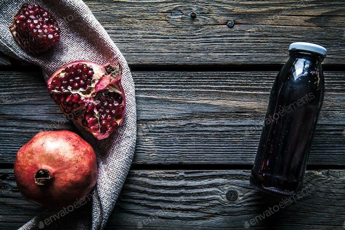 Granatapfel und Flaschen von Essenz oder Tinktur auf rustikalem Holztisch