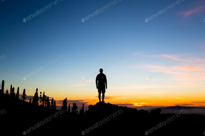 Man celebrating sunset looking at view in mountains
