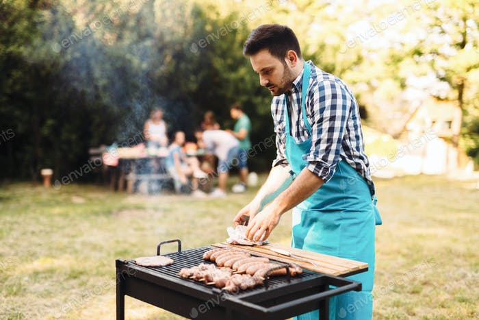 Handsome male prepares barbecue in a forest