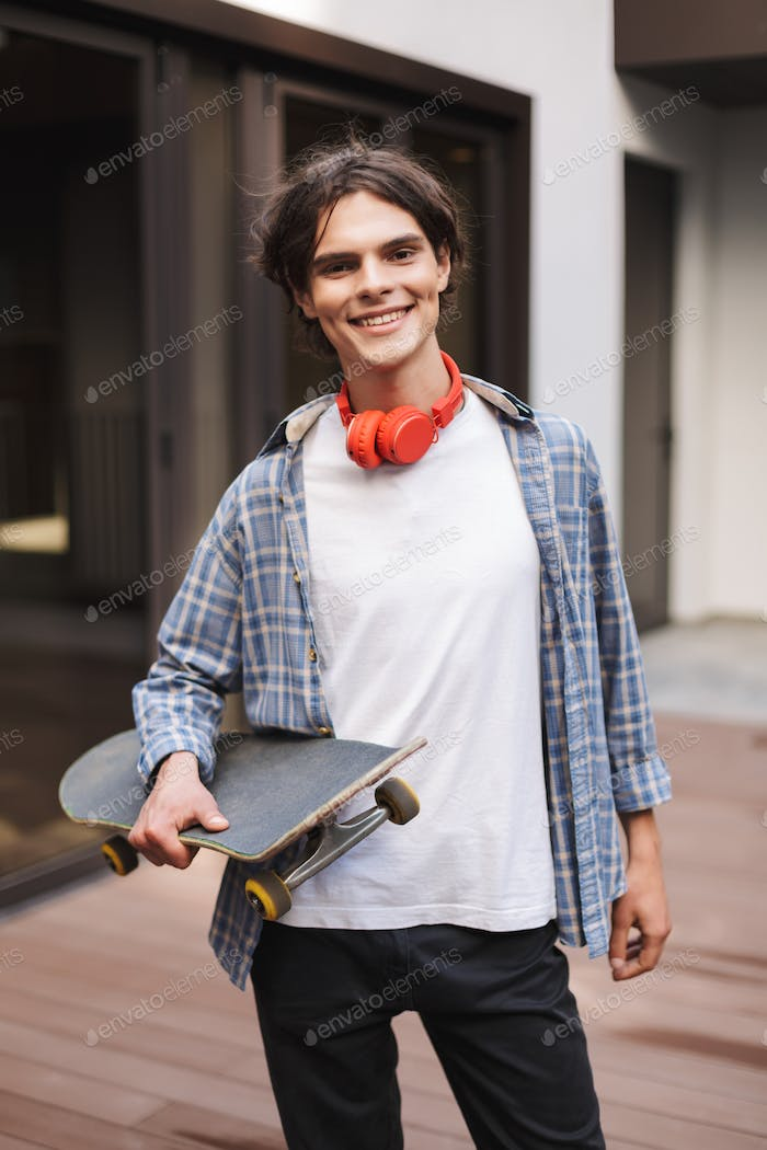 Young smiling man with red headphones standing and holding skateboard while joyfully