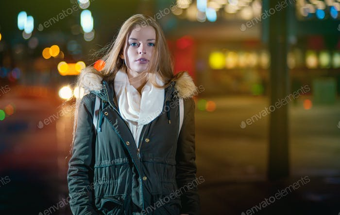 Night portrait of young girl in colorful city lights