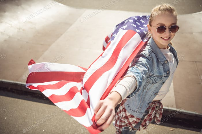 Young Blonde Girl in Sunglasses Holding American Flag While Standing on Ramp at Skateboard Park