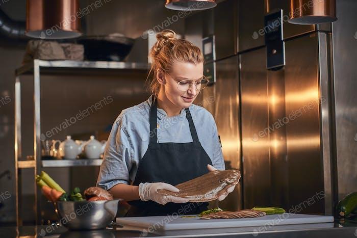 European beautiful female chef in a dark restaurant kitchen