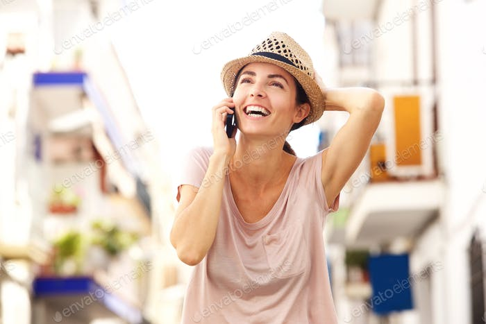 Close up cheerful young woman walking outdoors and talking on cell phone