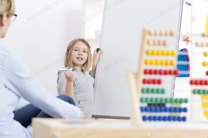 Girl writing on whiteboard