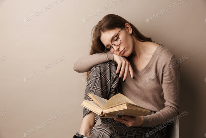 Photo of charming sad woman reading book and sitting on chair