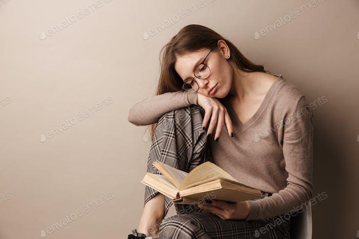 Foto von charmanten traurigen Frau Buch lesen und sitzen auf Stuhl