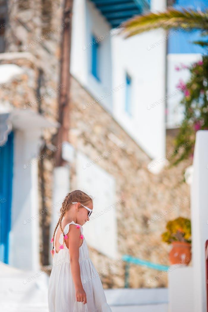 Entzückendes kleines Mädchen auf der Straße des typischen griechischen traditionellen Dorfes auf Mykonos Insel, in Griechenland