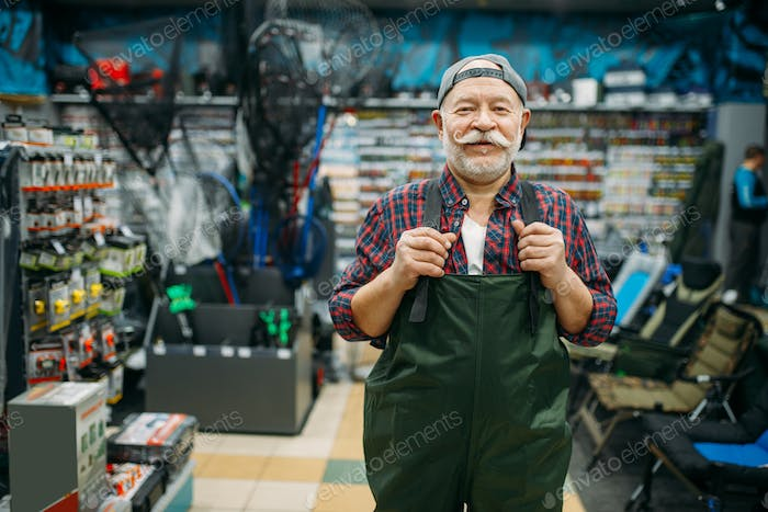 Fisherman tries on rubber jumpsuit in fishing shop