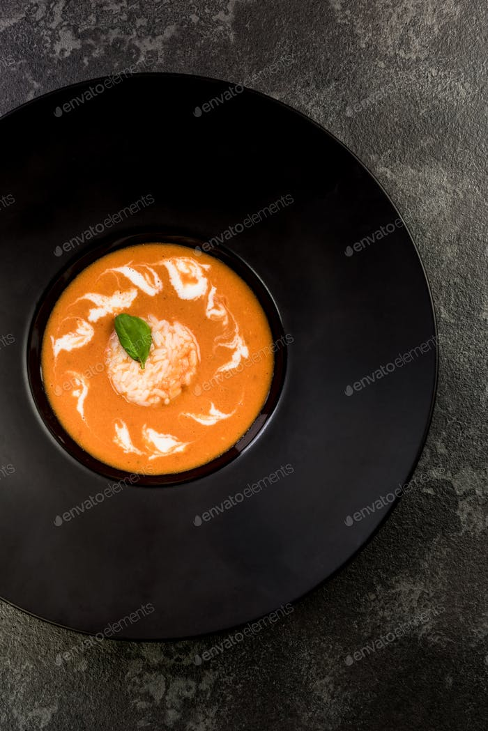 Homemade tomato soup served on dark plate