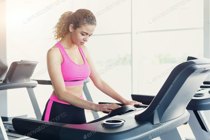 Attractive woman on treadmill in fitness club, healthy lifestyle