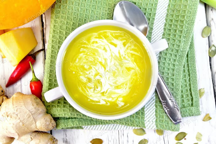 Soup-puree pumpkin with cream in white bowl on green napkin top
