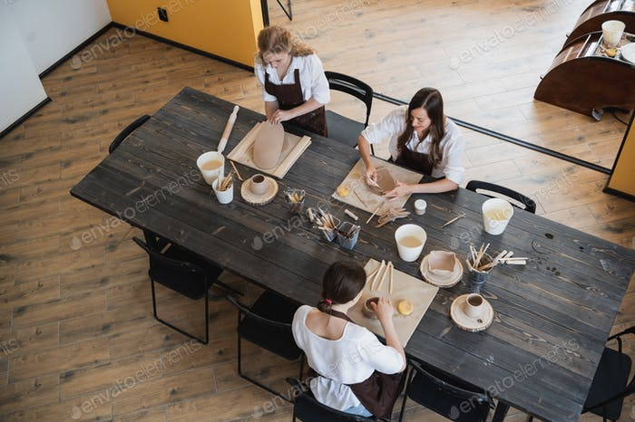 Three women in aprons sitting by table, kneading clay and making earthenware at lesson