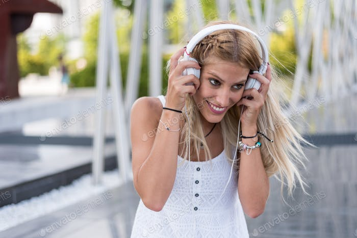Happy blonde woman with headphones listening music outdoors