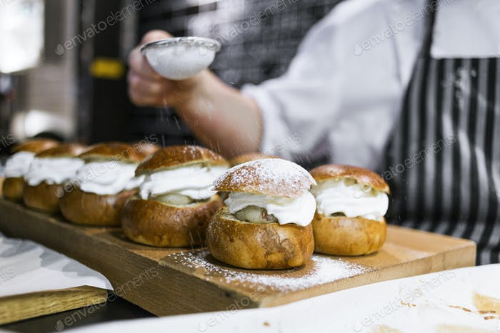 Cropped image of chef dusting icing sugar on cream buns in kitchen