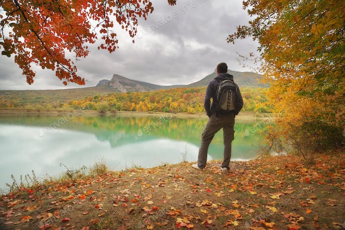 Man standing alone on the autumn pond.