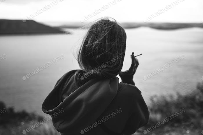 Back of hipster girl in windbreaker holding cigarette