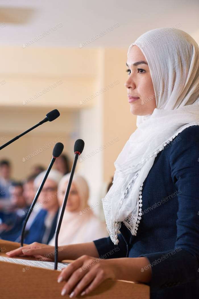 Young pretty confident muslim female delegate in hijab