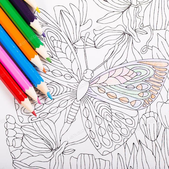 Разноцветные карандаши и книжка-раскраска для взрослых