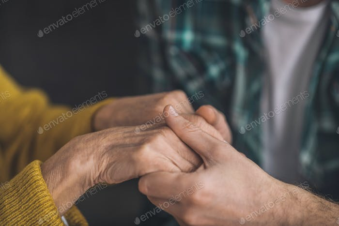 Young man tenderly holding his moms hands
