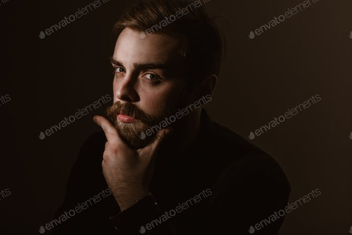 Sepia portrait of a stylish man with a beard and stylish hairdo dressed in the black shirt on the
