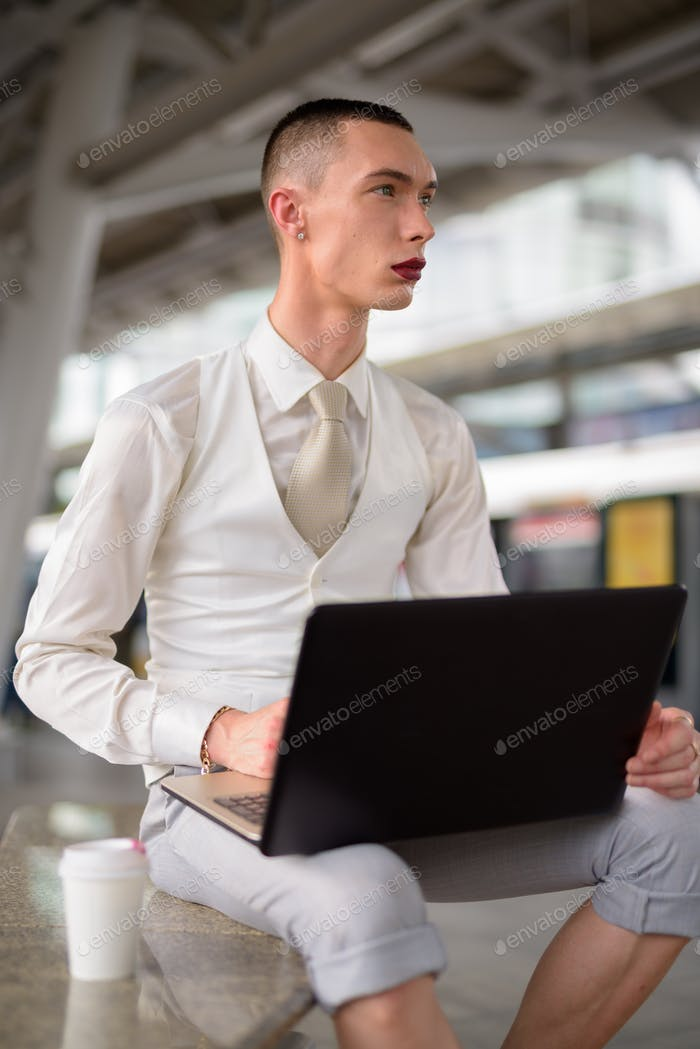 Young androgynous homosexual LGTB businessman using laptop computer