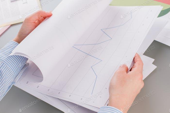 Las manos de la mujer de negocios que trabajan con gráficos y diagramas.