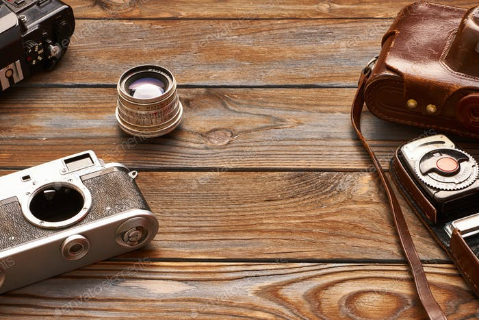 Vintage cameras and lenses on wooden background