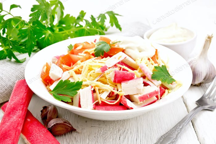 Salad of surimi and tomatoes on wooden table