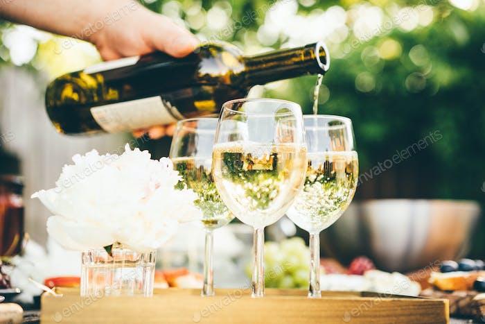 Weißwein wird in Glas gegossen. Konzept der Feier, Party im Freien.